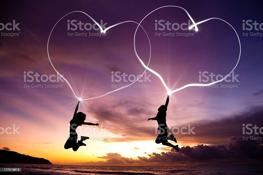 young couple jumping and drawing hearts stock photo