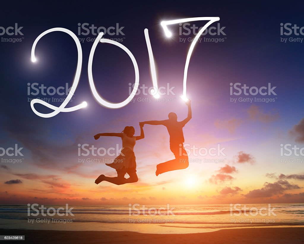 young couple jumping in 2017 stock photo