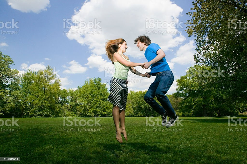 Young couple jumping in park, holding hands, laughing stock photo