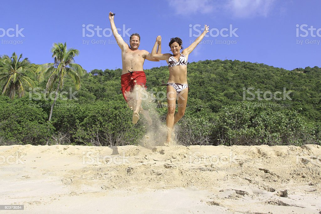 Young couple jumping on a tropical beach royalty-free stock photo