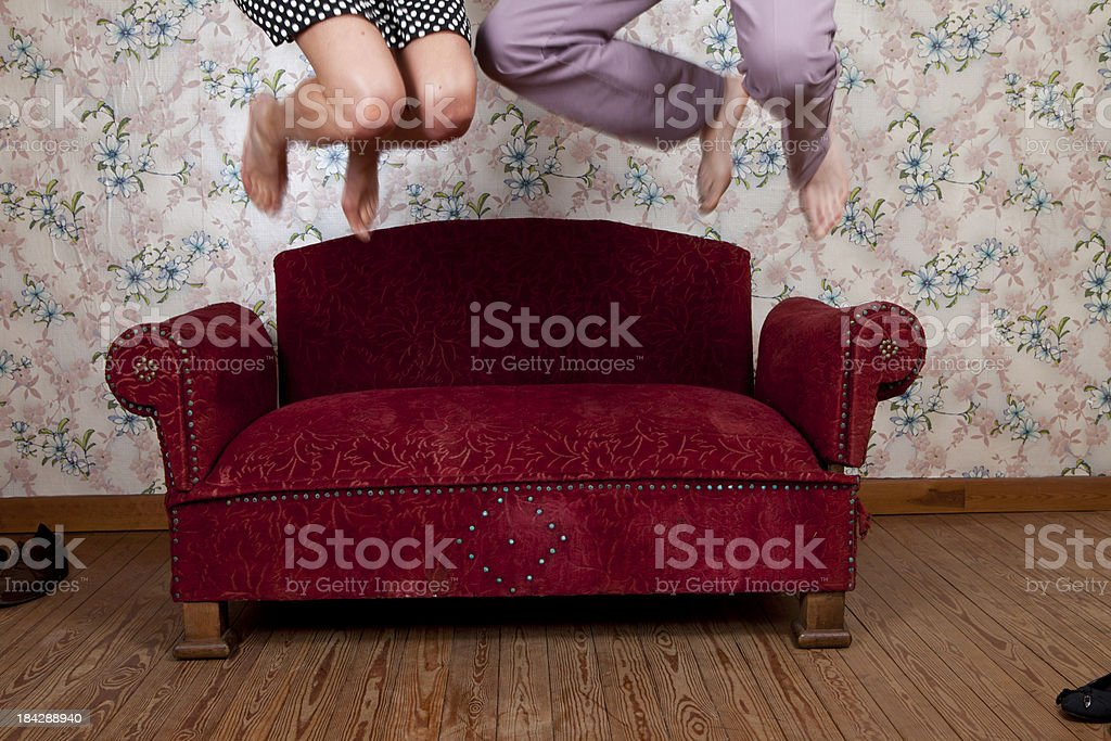 Young couple jumping on old school couch stock photo