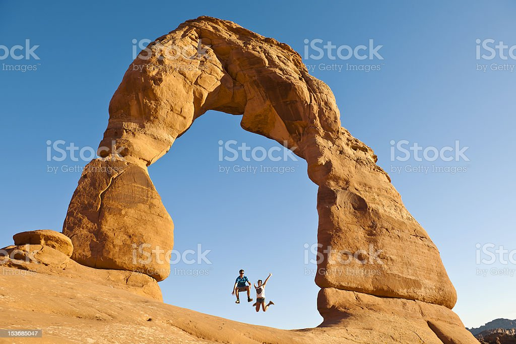 Young Couple Jumping under Delicate Arch Utah USA stock photo