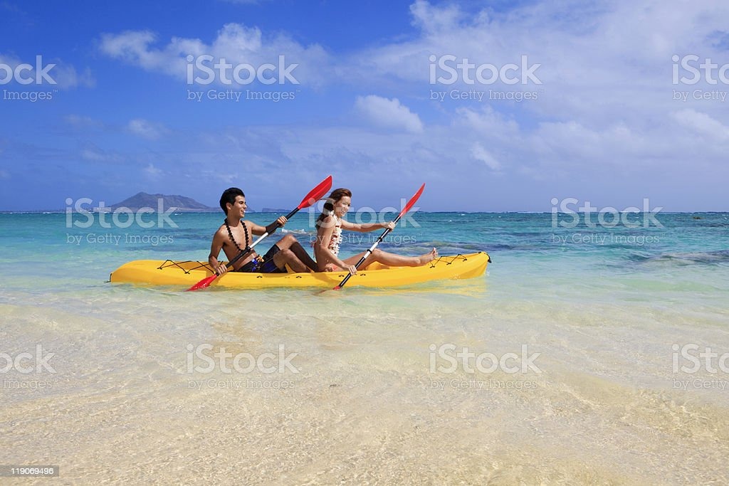 young couple kayaking in hawaii royalty-free stock photo