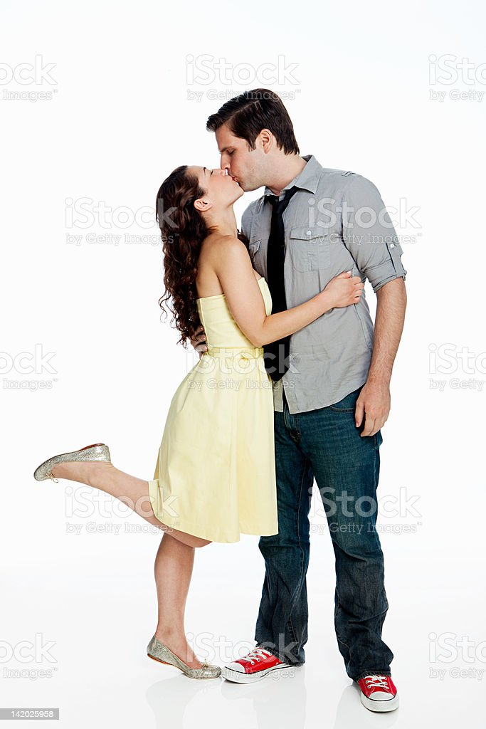 Young couple kissing against white background stock photo