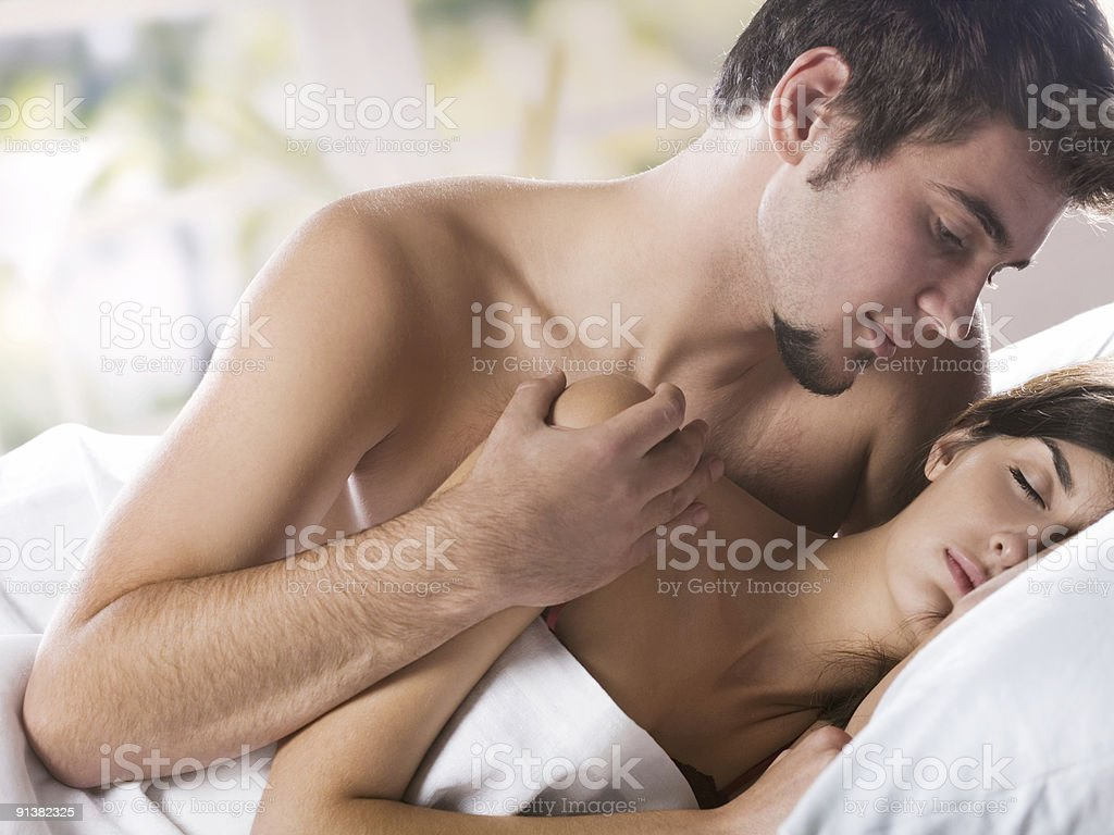 Young couple kissing and hugging on the bed in bedroom royalty-free stock photo