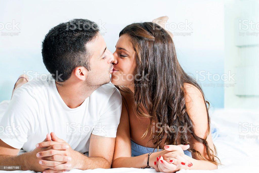 Jeune couple embrasser dans la chambre à coucher. photo libre de droits