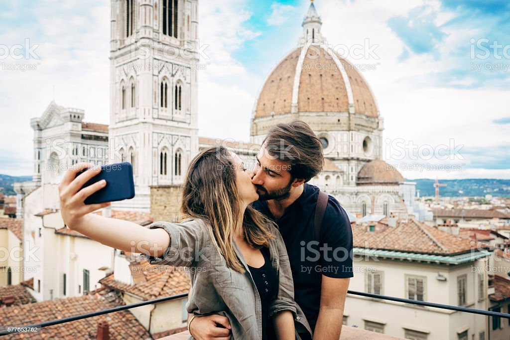 Young couple kissing in front of Florence's cathedral stock photo