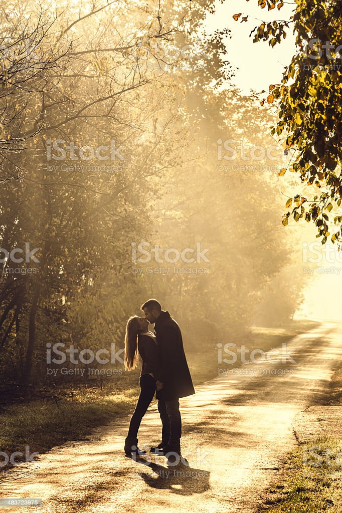 young couple kissing in the autumn sunshine royalty-free stock photo