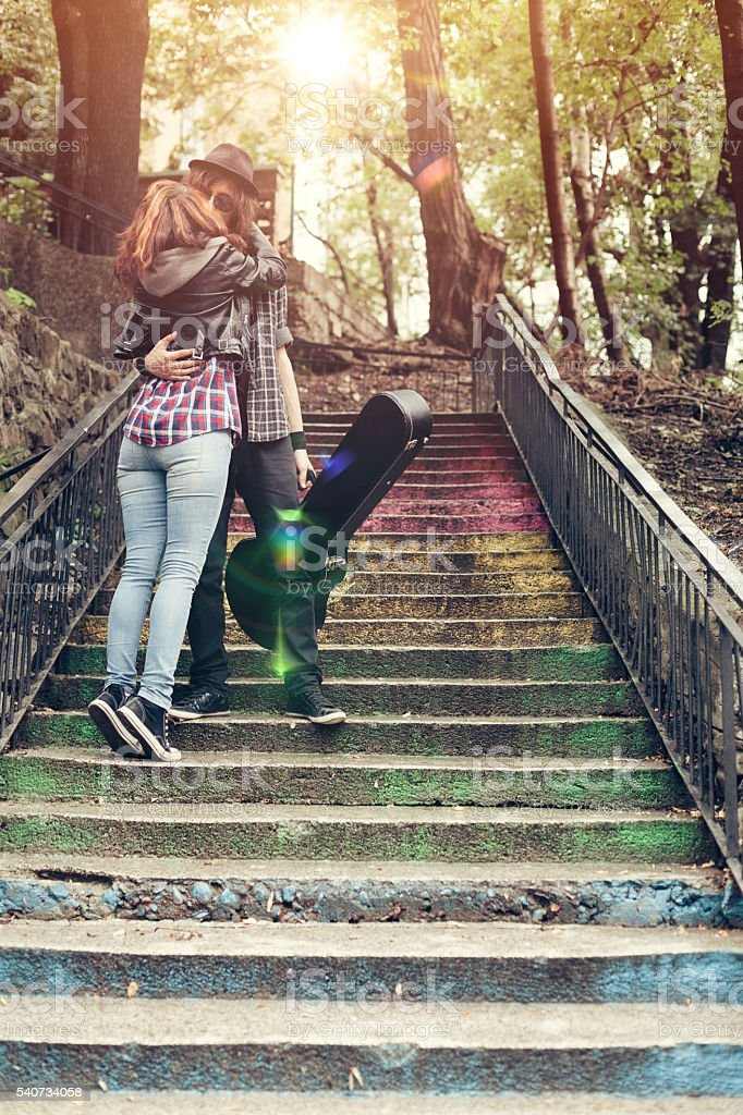 Young couple kissing in the park stock photo