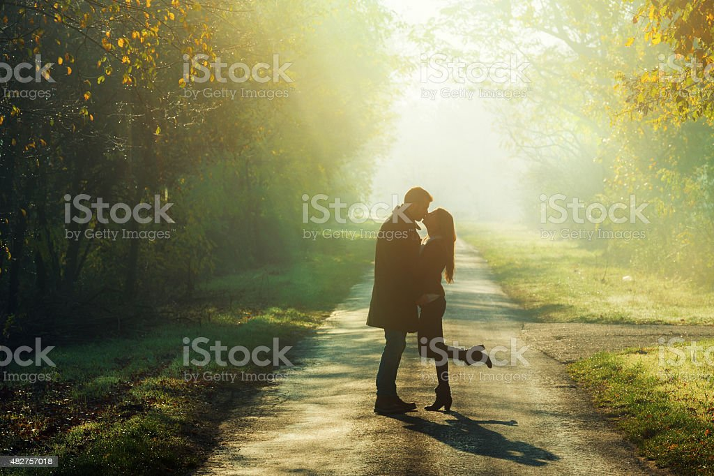 young couple kissing in the sunshine stock photo