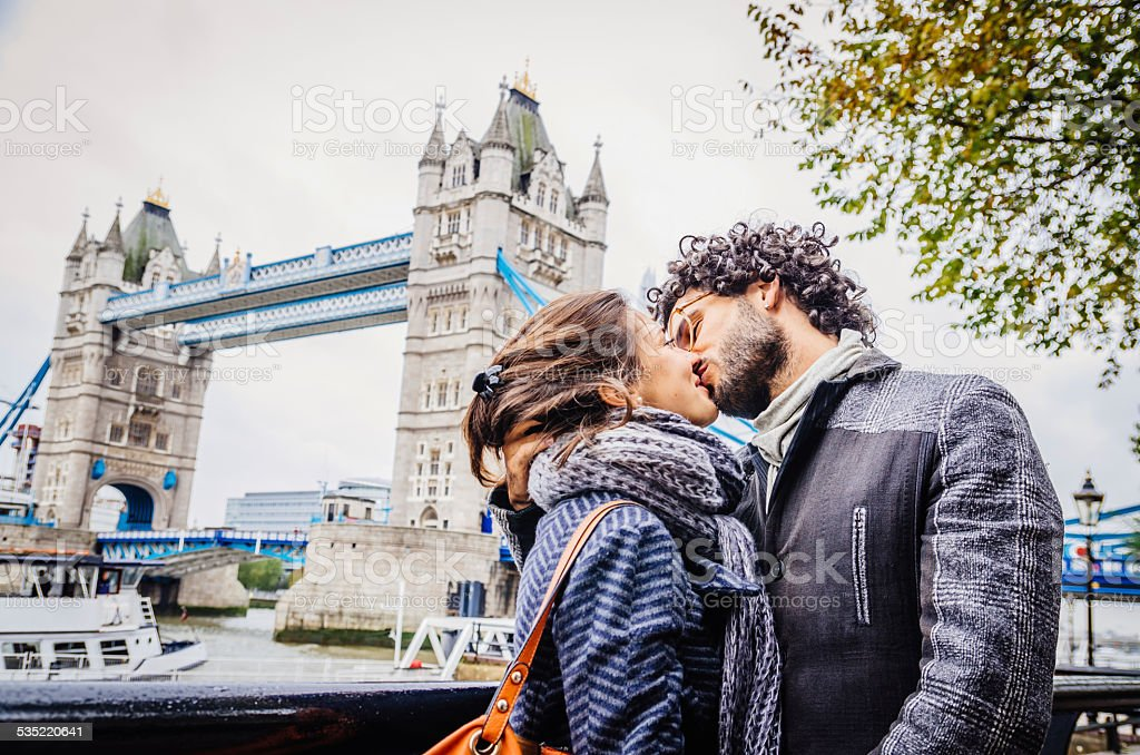 Young Couple Kissing Near Tower Bridge In London stock photo