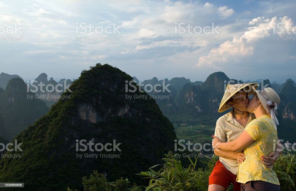 Young couple kissing on top of the mountain royalty-free stock photo
