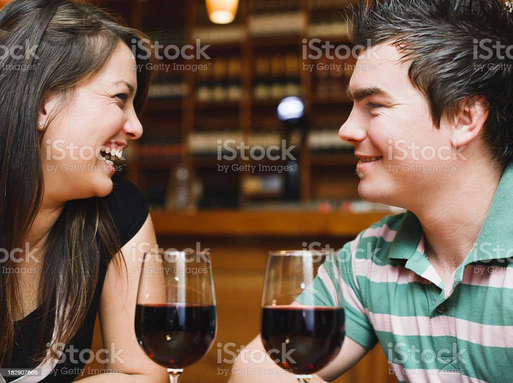 Young couple laugh together over red wine in trendy bar royalty-free stock photo