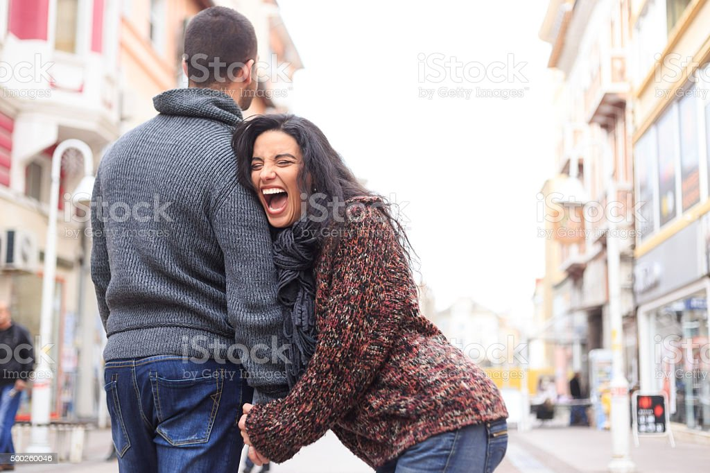 Young couple laughing and holding hands stock photo