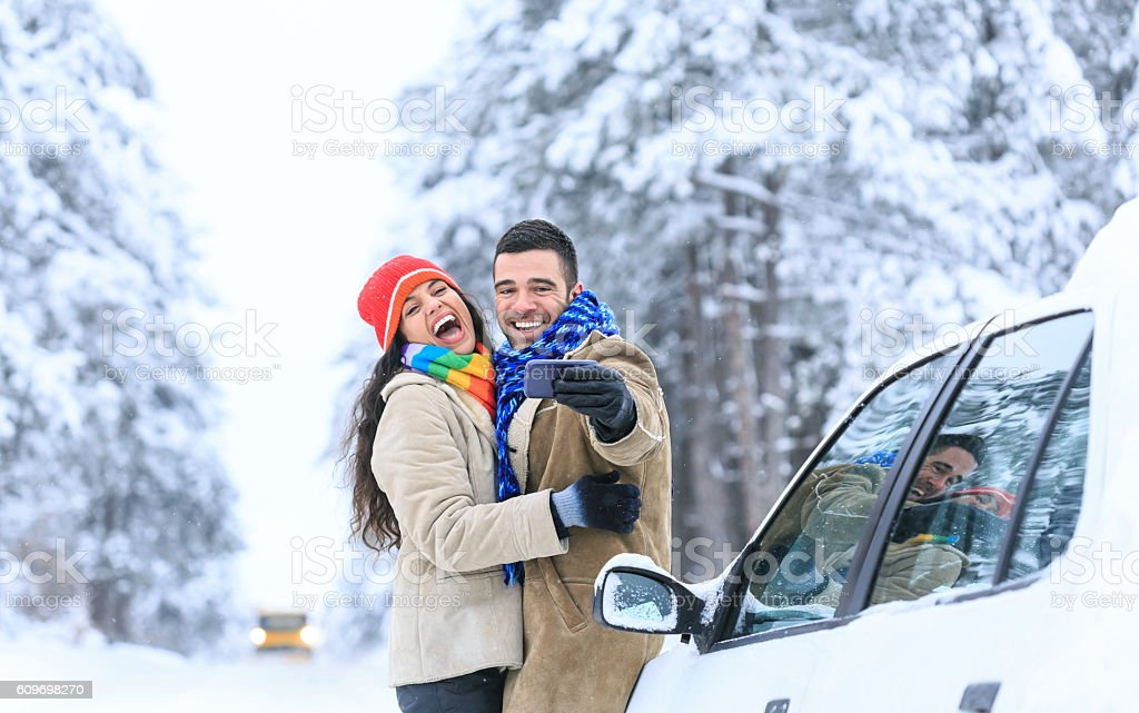 Young couple laughing and making selfie on snow footpath stock photo