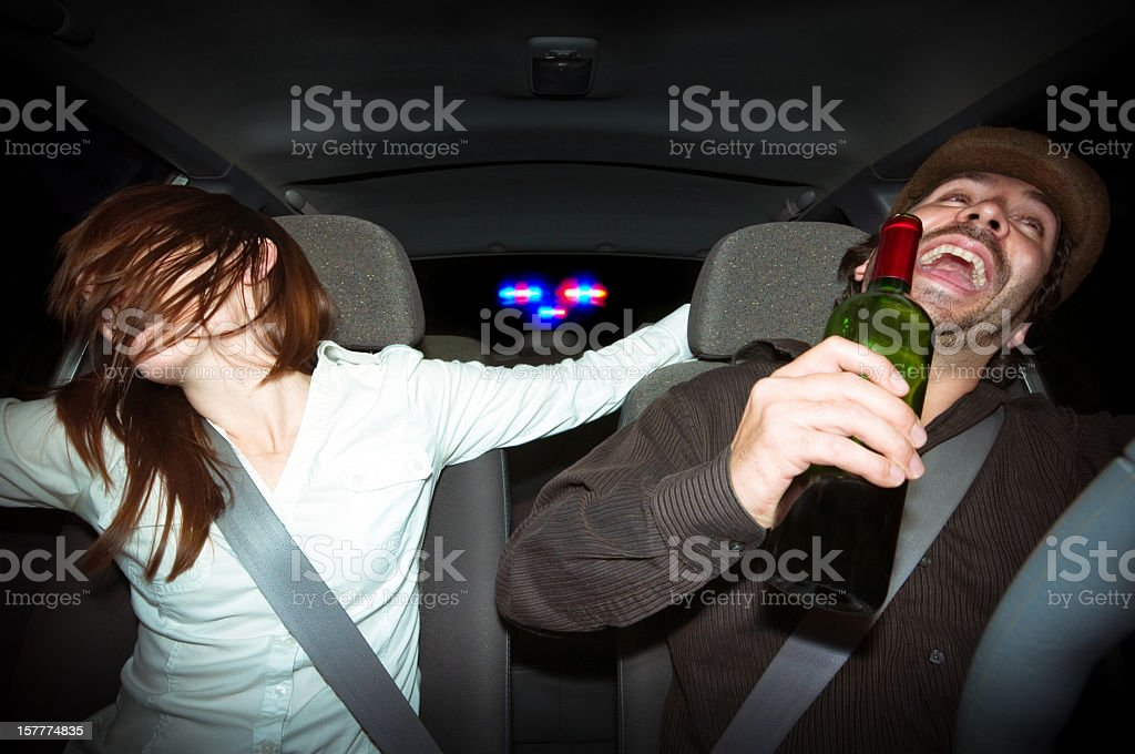 Young couple laughing in car while holding a bottle of wine stock photo