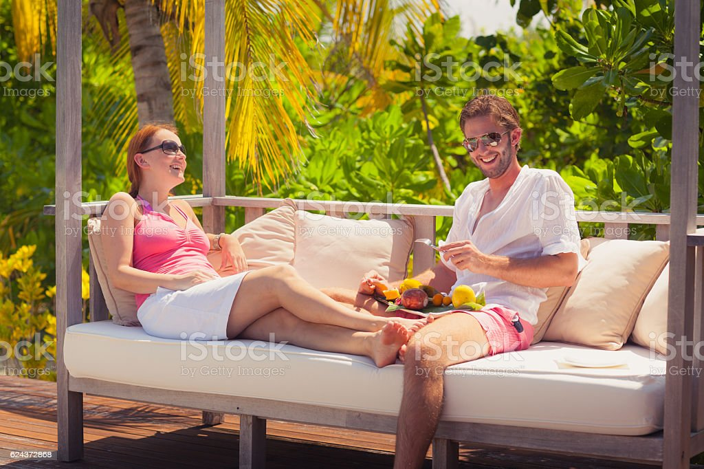 young couple laughing tropical island relax fruits stock photo
