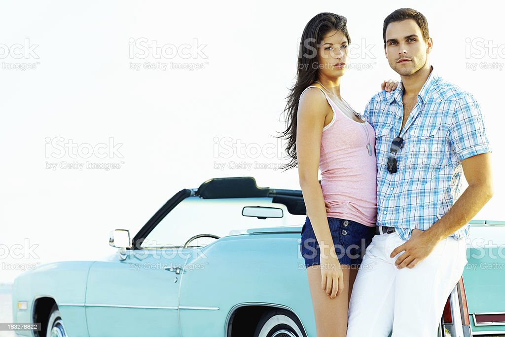 Young couple leaning against convertible car - copyspace royalty-free stock photo