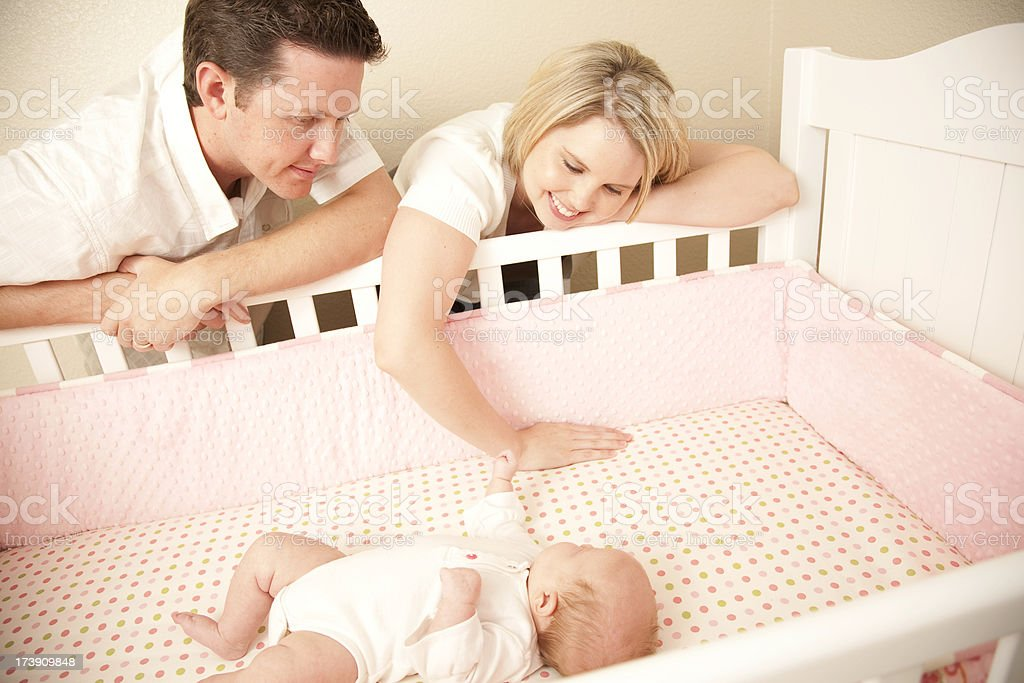 Young Couple leaning down close to their baby in crib royalty-free stock photo