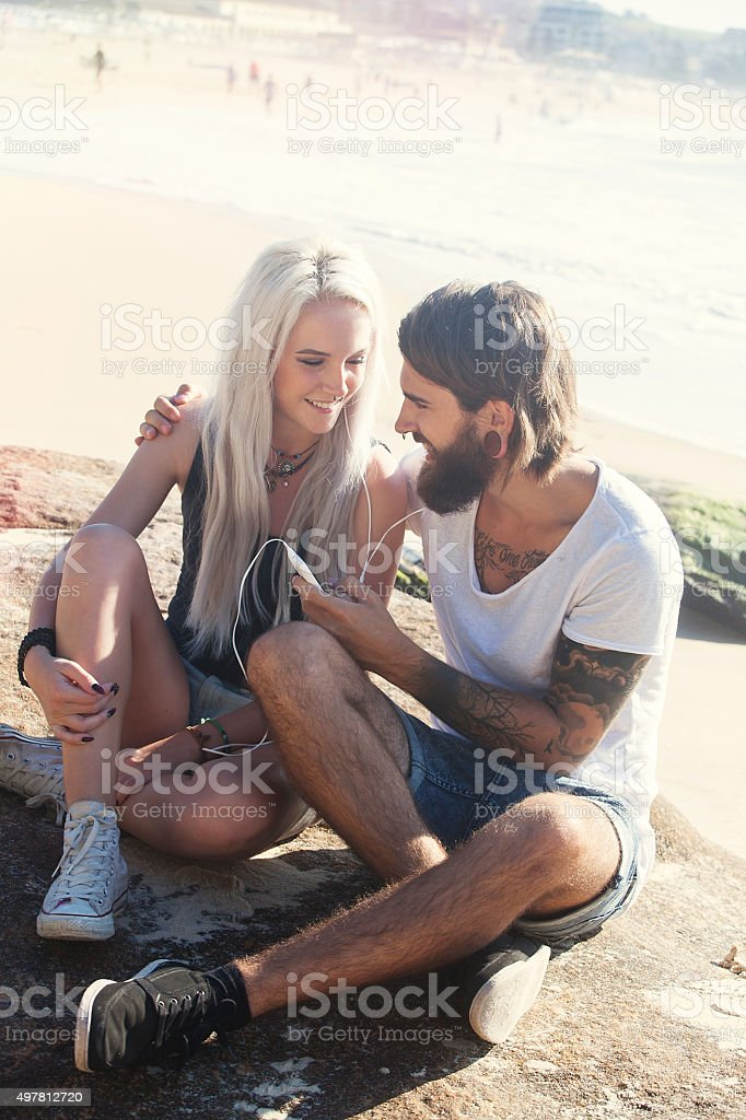 young couple listening together to music stock photo