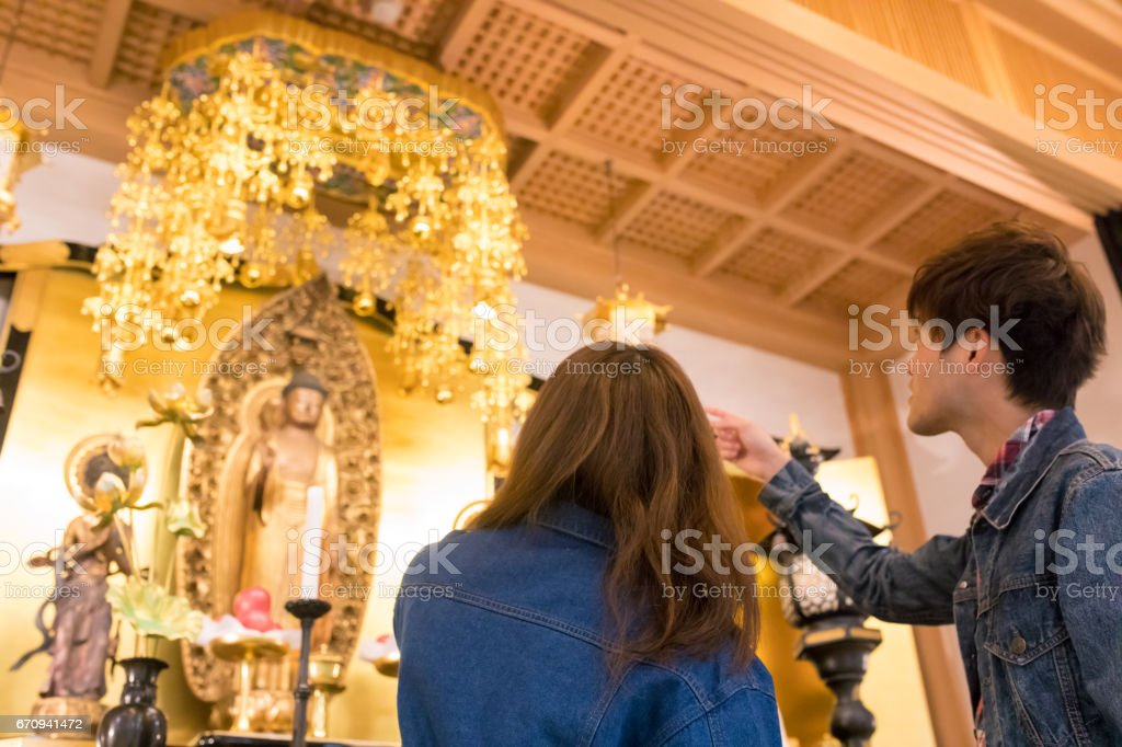 Young couple looking at Buddha statues in Hyakumanben Chionji temple, Kyoto stock photo