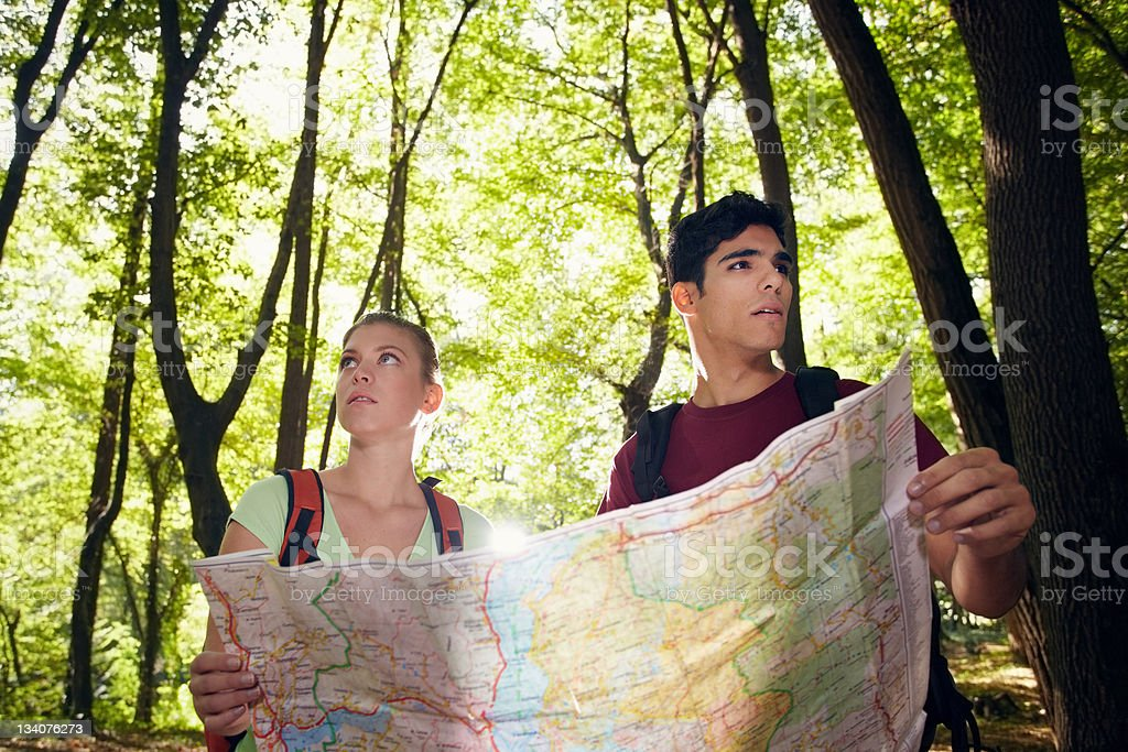 young couple looking at map during trek stock photo