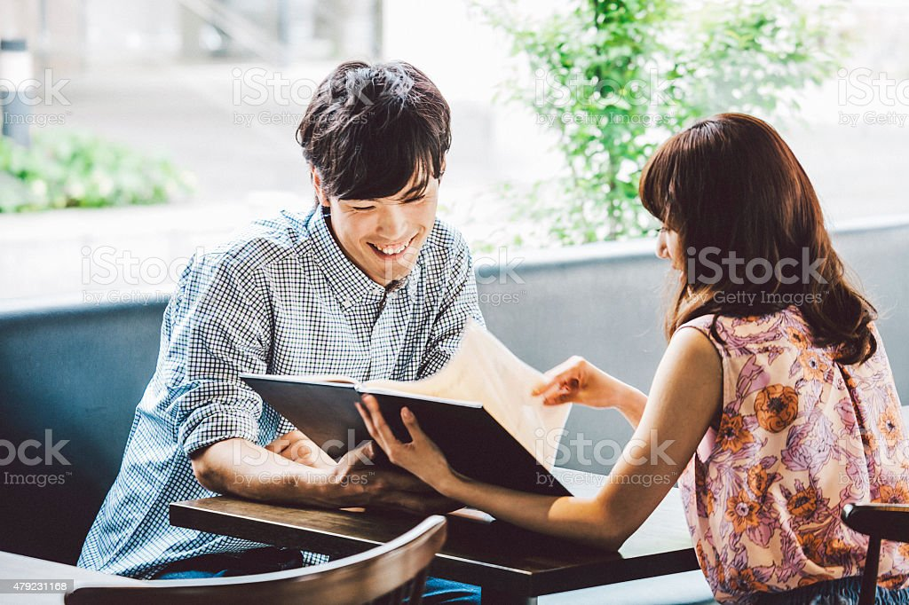 Young couple looking at menu in cafe. stock photo