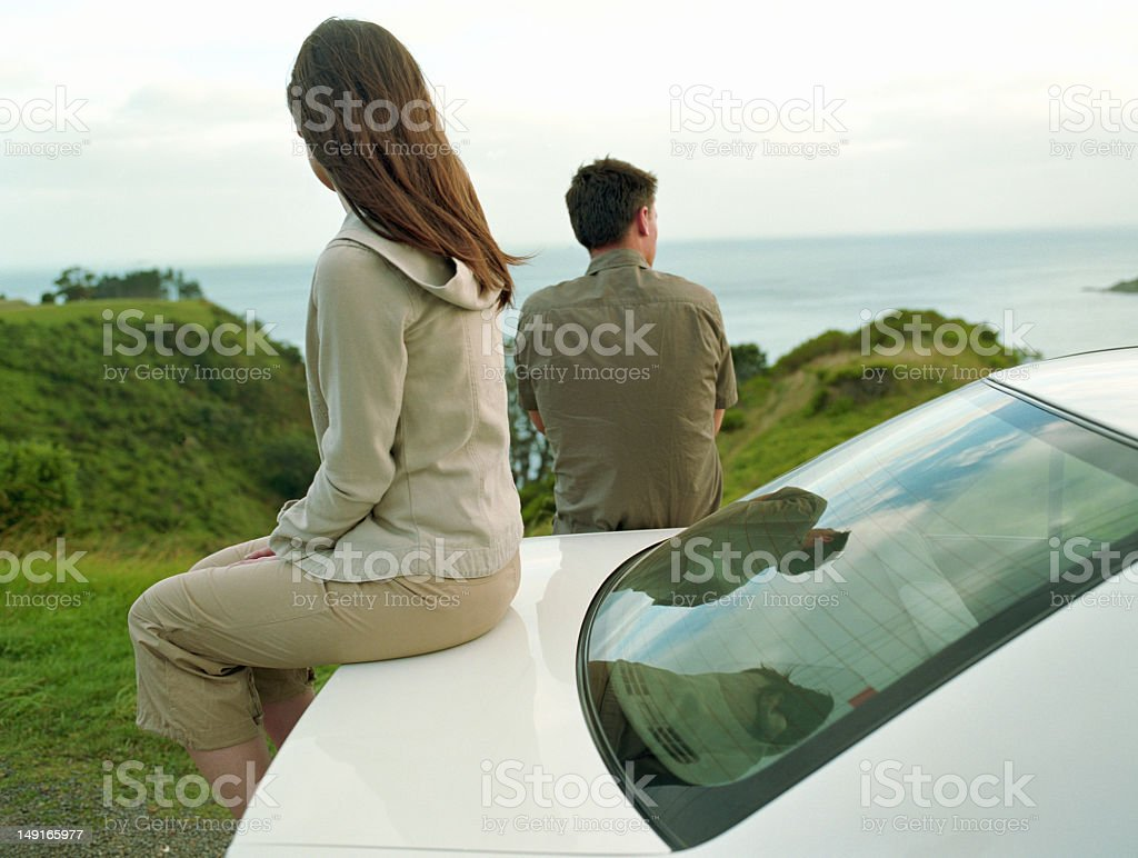 Young couple looking at sea, woman sitting on trunk royalty-free stock photo