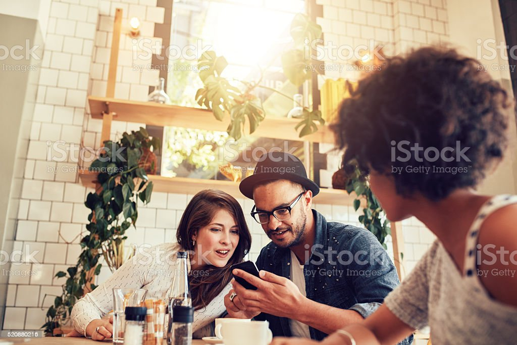 Young couple looking at smart phone while sitting in cafe stock photo