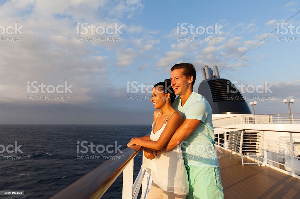 young couple looking at sunrise on cruise ship stock photo