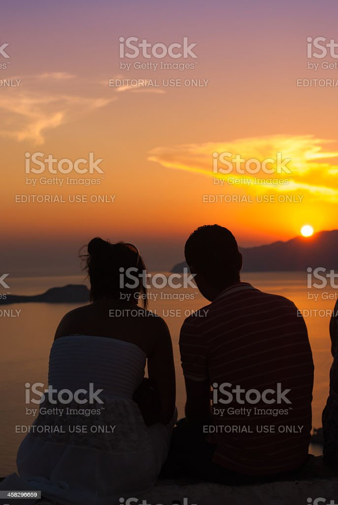 Young couple looking at sunset in Milos, Cyclades stock photo