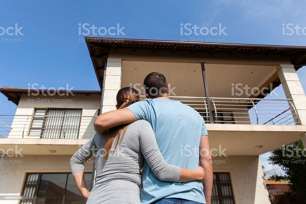 young couple looking at their new house stock photo