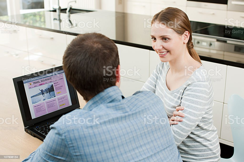 Young couple looking at travel insurance on laptop stock photo