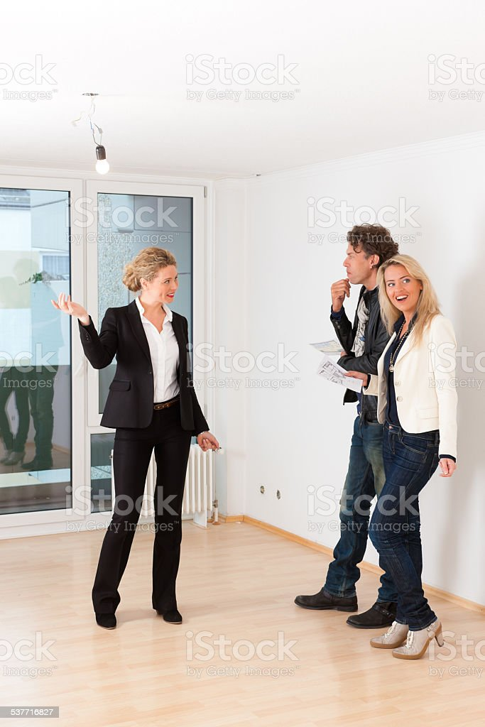 Young couple looking for real estate with female realtor stock photo