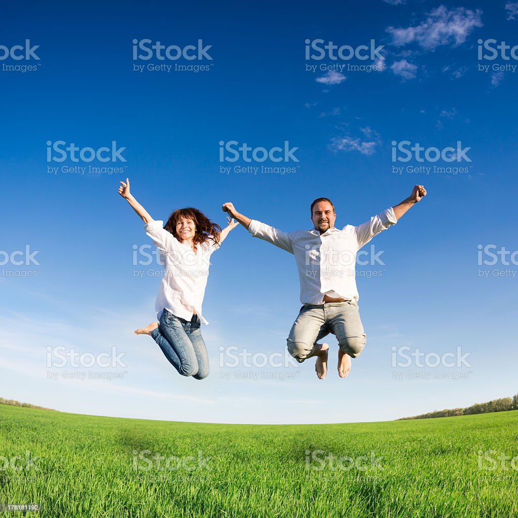 Young couple looking happy jumping in the air in a field stock photo