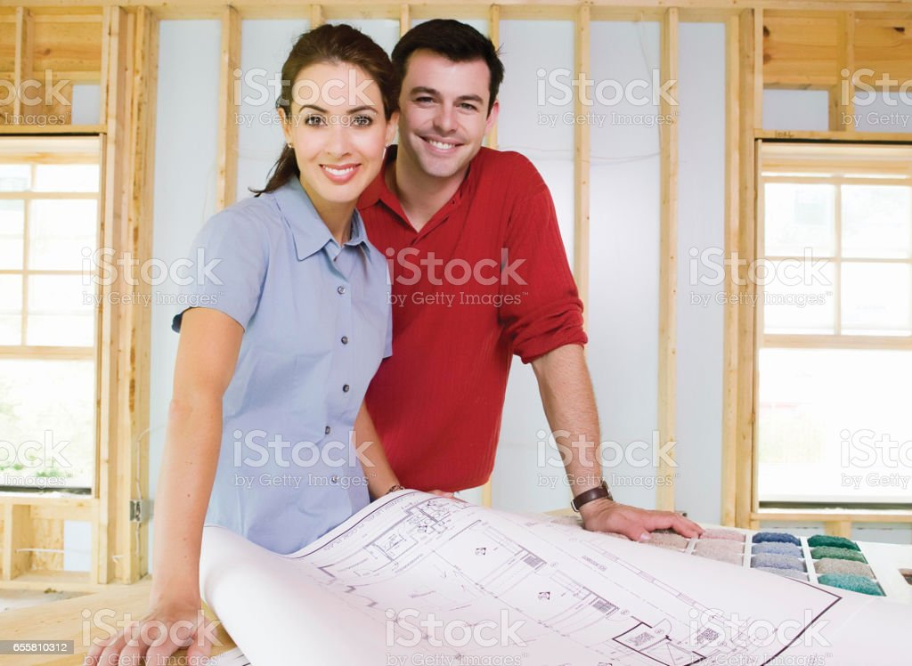 Young couple looking over construction blueprints with their home...