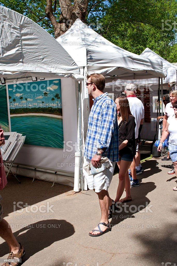Young Couple Looks At Paintings On Display In Arts Festival stock photo