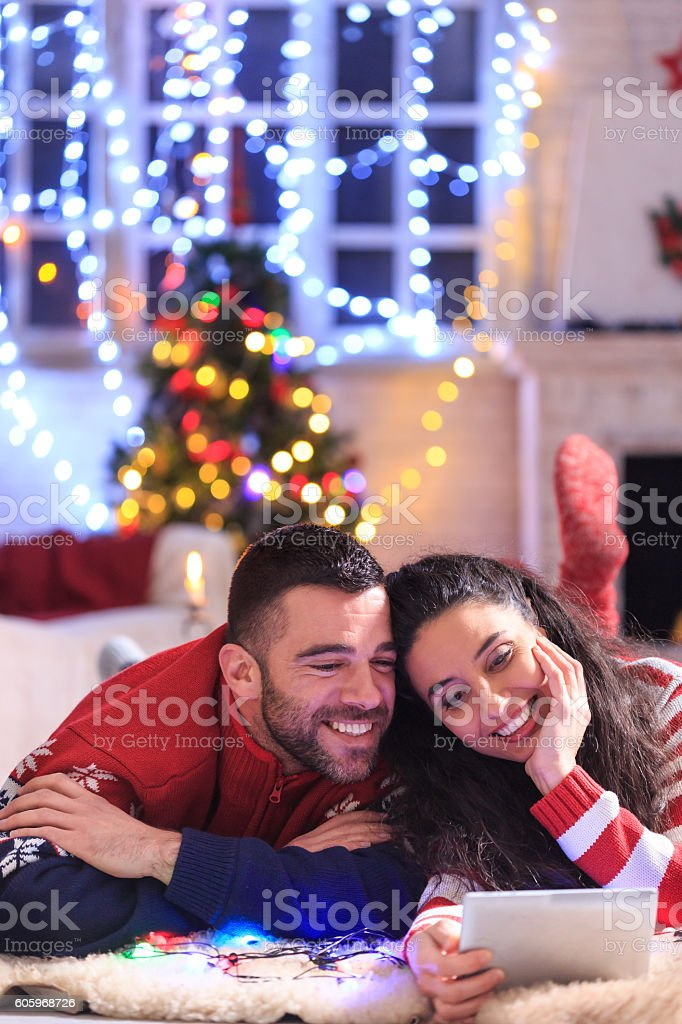 Young couple lying down and using digital tablet at home stock photo