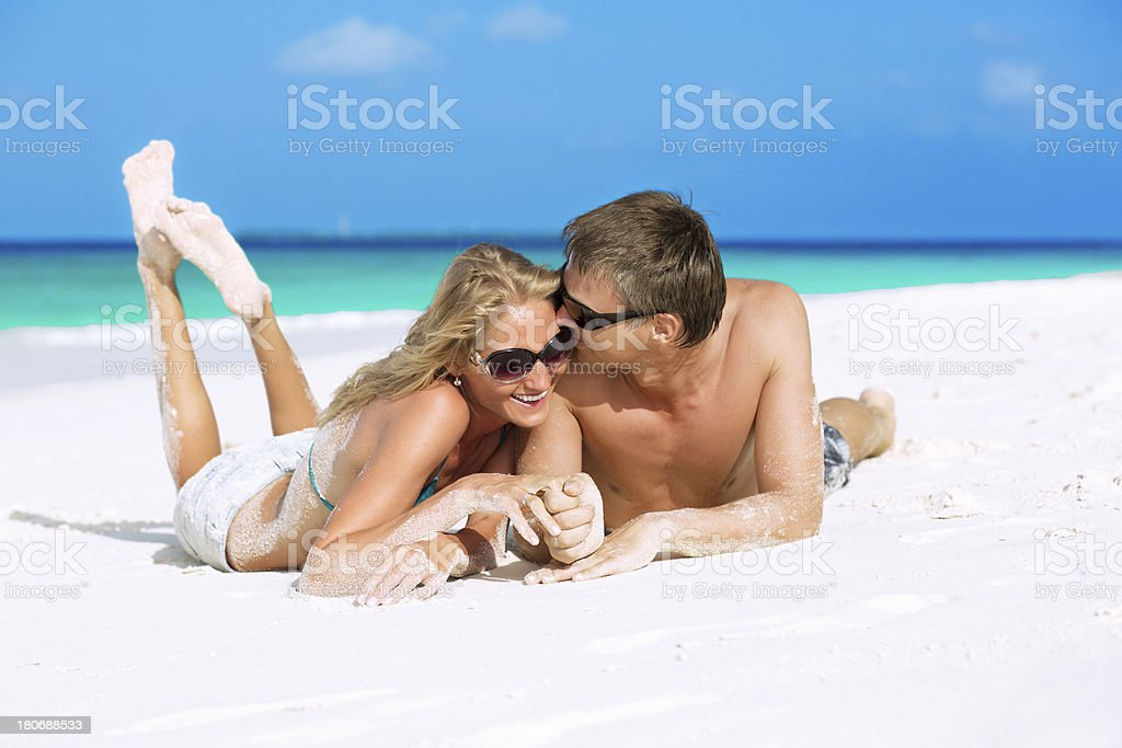 A young couple lying down in the sand royalty-free stock photo