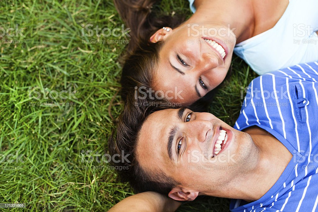 Young couple lying down on the grass stock photo