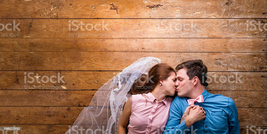 Young couple lying on a floor against wooden background stock photo