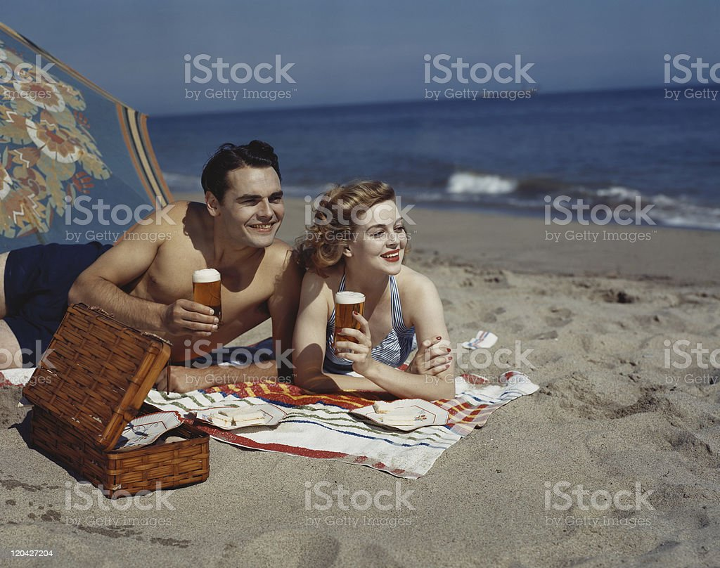 Young couple lying on beach with beer, smiling stock photo