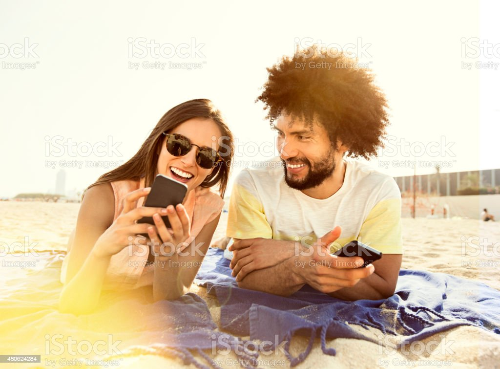Young couple lying on blanket on beach, using smart phone stock photo