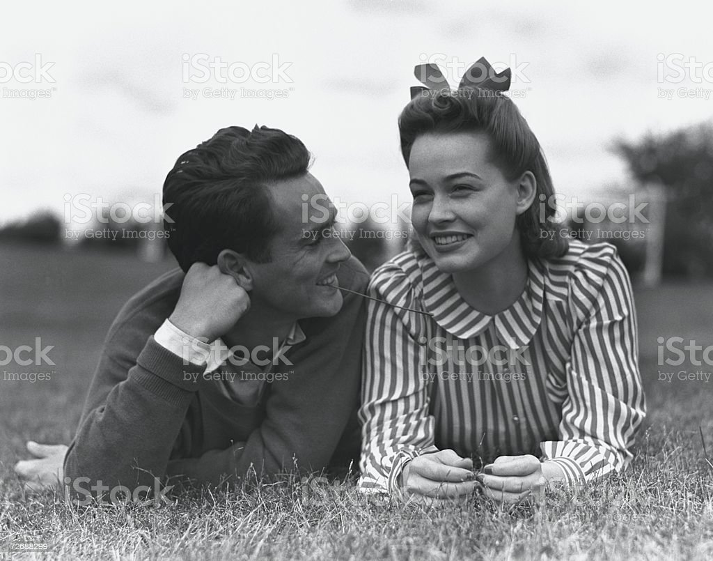 Young couple lying on grass stock photo