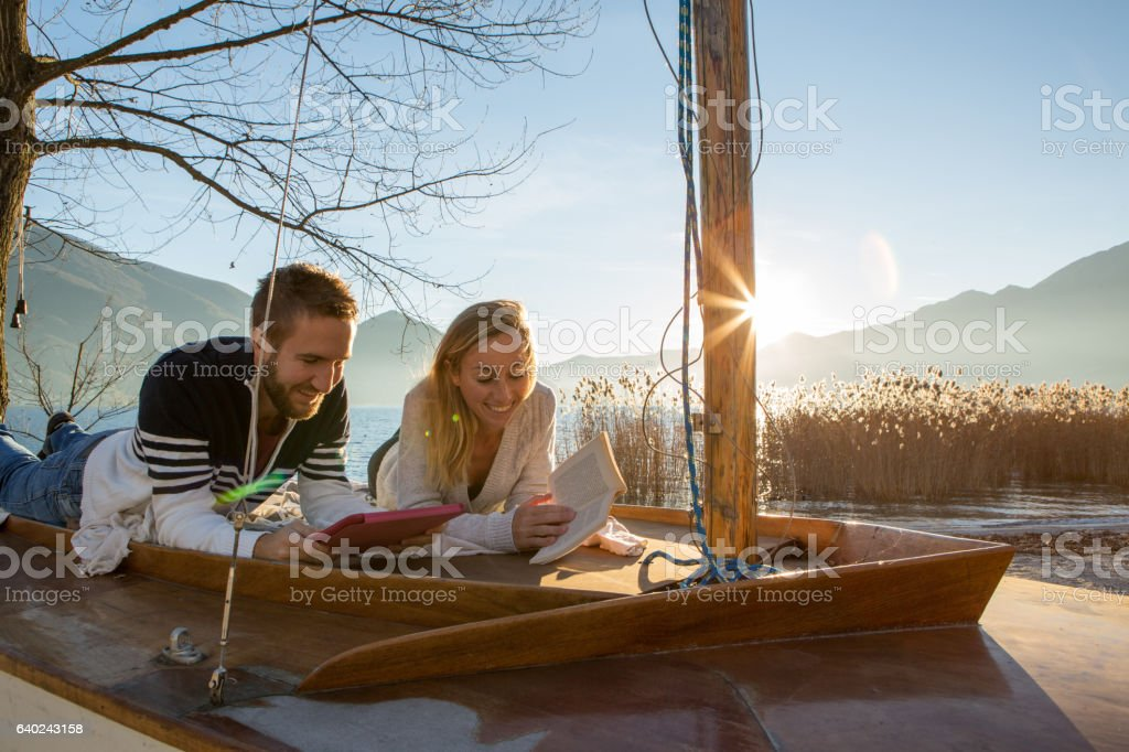 Young couple lying on sailboat above lake, relaxing stock photo