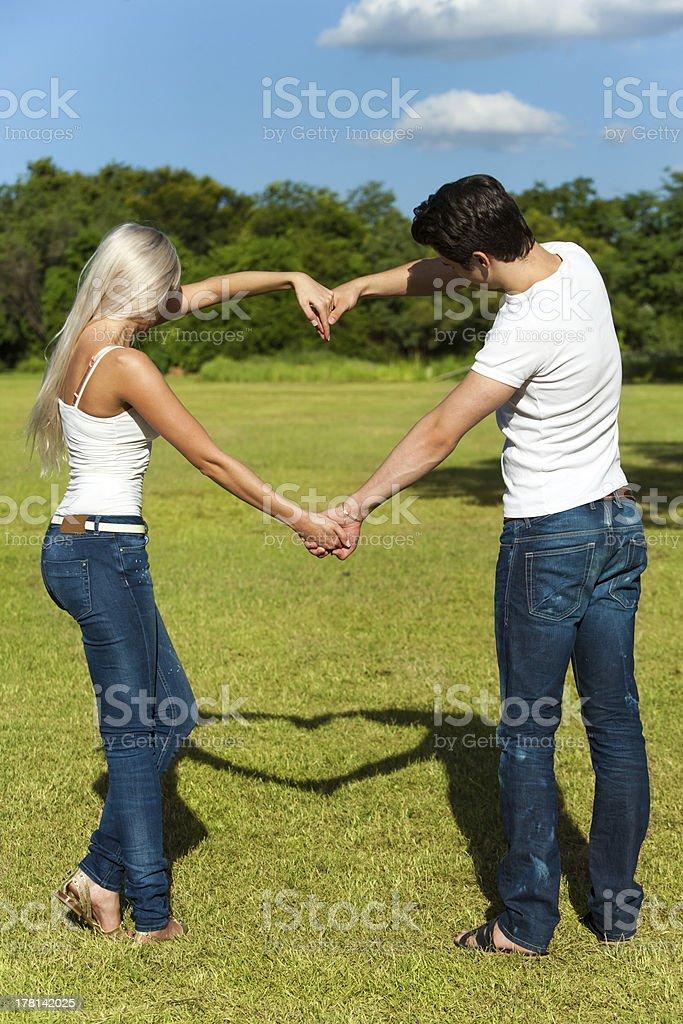 Jeune couple faisant l'amour signe avec bras. photo libre de droits