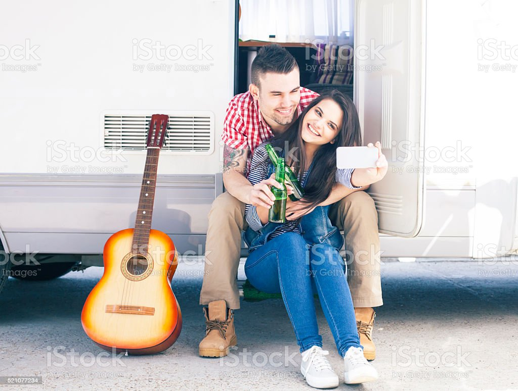 Young couple making selfie in front of a camper van stock photo