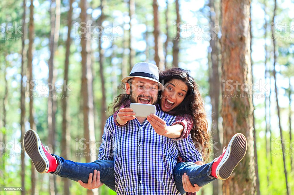Young couple making selfie in the forest stock photo