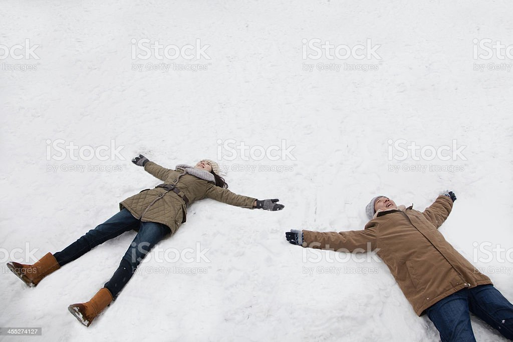 Young couple making snow angels stock photo