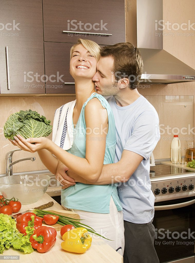 Young couple making vegetable salad in the kitchen royalty-free stock photo